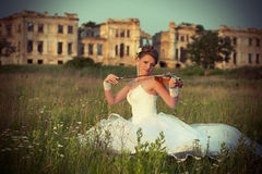 Bride with violin in front of ruins Stock Photo
