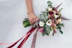 Wedding bouquet in bride`s hands. The bride is waiting for the groom. Wedding bouquet in bride`s hands Stock Photo