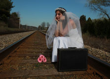 Bride waiting for train. Bride wearing a white wedding gown sitting waiting for the train royalty free stock photography
