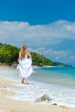Bride walking along sea coast Stock Photo