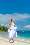 Bride walking along sea coast Royalty Free Stock Images