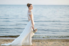 Bride walking along sea coast on sunset Stock Image