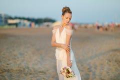 Bride walking along sea coast on sunset Stock Images