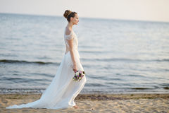 Bride walking along sea coast on sunset Stock Photo