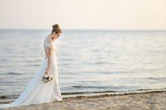 Bride walking along sea coast on sunset Royalty Free Stock Photo