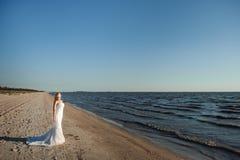 Bride walking along sea coast wearing beautiful dress royalty free stock photo