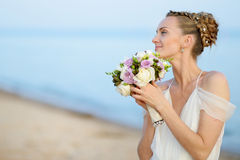 Bride walking along sea coast in wedding dress Stock Image