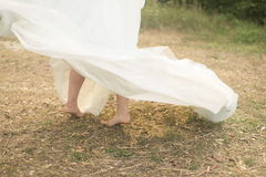 Bride walking barefoot. Happy bride dancing walking barefoot on a wedding day. Nice romantic beautiful dress, bare feet on the ground. Dress flying up in wind royalty free stock photography