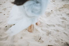 Bride walking barefoot. Happy bride walking barefoot on a wedding day at the beach. Nice romantic blue beautiful dress, bare feet in sand. Dress flying up in stock images