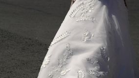 Bride walking in a city and waving dress. Bride walking in a city and waving white bridal dress stock video footage