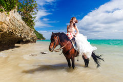 Bride walking with horse on a tropical beach Royalty Free Stock Image