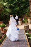 Bride walking to groom. A bride walking on a brick path with a package in her hand. she's going to see the groom for the first time Royalty Free Stock Photos
