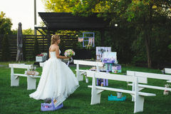 Bride Walking at Yard. Bride walking among decorated benches at yard Stock Photography