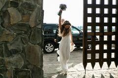 Bride walks like a winner in big wooden gates holding her bouque Stock Photo
