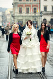 Bride walks with pretty bridesmaids along the tramways Stock Photo