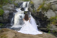 Bride at Waterfall. Bride looking at waterfall with veil stock photos
