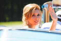 Bride Waving Hand. Sitting in cabriolet Royalty Free Stock Images