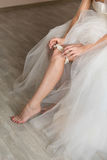 Bride wear the garter. The bride in a wedding dress on an elegant dress garter leg Royalty Free Stock Photography