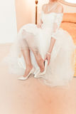 Bride is wear on her shoes Royalty Free Stock Photos