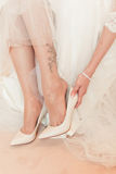 Bride is wear on her shoes Royalty Free Stock Images