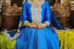 Bride Wearing a blue dress sitting on an altar, head not seen Stock Images