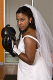 Bride wearing boxing gloves. A young African American bride wearing black boxing gloves as if she is trying to show she is ready for a fight to show who the boss Royalty Free Stock Images