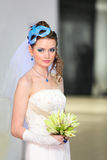 Bride wearing in dress with mask in hairdo. Beautiful young bride wearing in white dress with blue makeup and mask in hairdo royalty free stock image