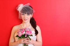 Bride wearing dress and short veil holds bouquet. Bride wearing white dress and short veil holds bouquet of roses and looks at camera on red background Stock Image