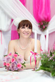 Bride wearing dress sits at table with candles stock photo