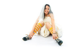 Bride wearing old blue sporting shoes. Funny young beautiful bride wearing old blue sporting shoes and colorful socks Stock Image