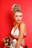 Bride wearing in original dress witn bouquet. Beautiful young bride wearing in original dress witn bouquet of roses on red background Royalty Free Stock Images