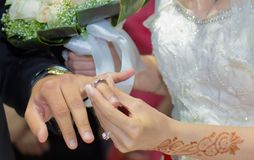 The bride is wearing a ring on the hands of a man. Bride is wearing a ring on the hands of a man Royalty Free Stock Image