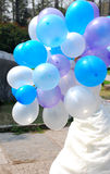 Bride wearing  wedding dress with color balloon. In outdoor Royalty Free Stock Photo