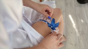 Bride wearing wedding garter. The bride wears a garter on the leg. Close-up of young bride putting on white grater. Morning of young beautiful bride. Woman Royalty Free Stock Image