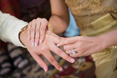 The bride wearing a wedding ring for her groom Stock Photo