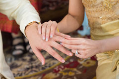 Bride wearing a wedding ring for her groom Stock Images