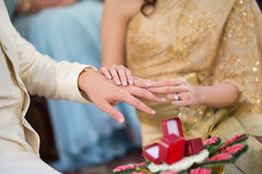 Bride wearing a wedding ring for her groom Stock Photo