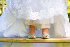 Bride Wearing Wedding Shoes. Blue wedding shoes shown to the camera by the bride as she lifts up the bottom of her dress on her wedding day Stock Images