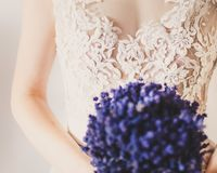 Bride with Flowers. Bride wearing white dress holding beautiful bouquet of blue or violet flowers Royalty Free Stock Image