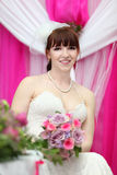 Bride wearing white dress holds bouquet royalty free stock photo