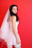 Bride wearing in white short dress on red Stock Image