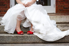 Bride wearing white wedding dress and red shoes Stock Photo