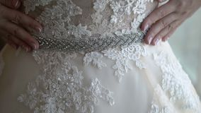 Bride wears belt on wedding dress. Closeup stock footage