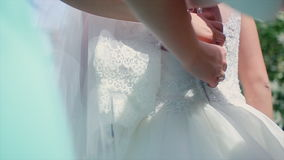 Bride Wears a Dress. Morning of the bride, the bride wears a dress, bridesmaid corrects bow on a dress, a wedding, a beautiful dress stock footage