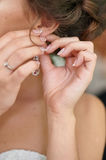 Bride wears an earring, close-up Royalty Free Stock Photos
