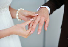 Bride wears a gold ring to the groom wedding Stock Image