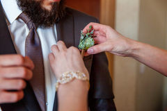 The bride wears a groom boutonniere Stock Photo
