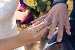 The bride wears a ring on the finger of the close-up Stock Photo