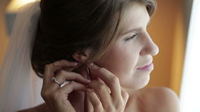 The bride wears a wedding earring. Close up. The bride wears a wedding earring stock video
