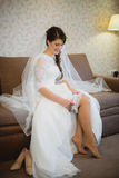 The bride wears a wedding garter on leg. The bride wears a wedding garter on the leg on the bed Stock Photography